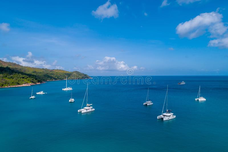 Spectacular aerial view of some yachts and small boats floating on a clear and turquoise sea, Seychelles in the Indian Ocean.Top stock photography