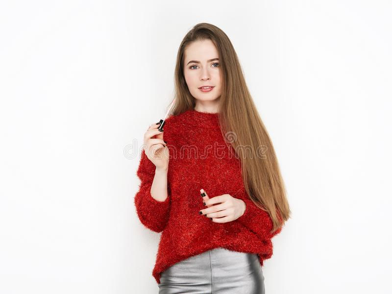 Spectacular blonde woman in red blouse silver leather pants posing with lip glow balm in front of white wall. Graceful girl gorgeo royalty free stock photo