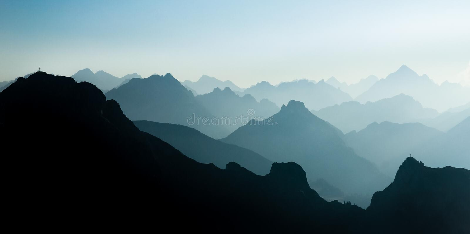 Spectacular blue and cyan mountain ranges silhouettes. Summit crosses visible. Blue and cyan mountain ranges silhouette with bright back light. Tirol, Austria royalty free stock photography