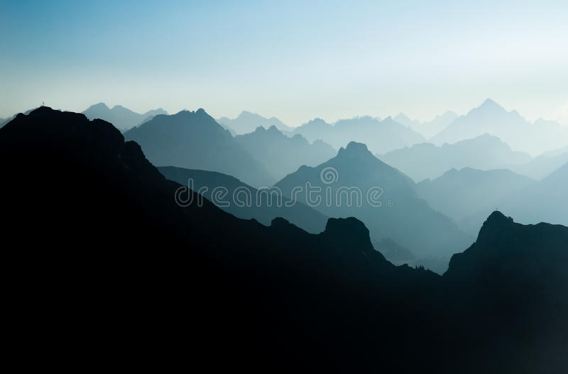Spectacular blue and cyan mountain ranges silhouettes. Summit crosses visible. Blue and cyan mountain ranges silhouette with bright back light. Tirol, Austria stock photography