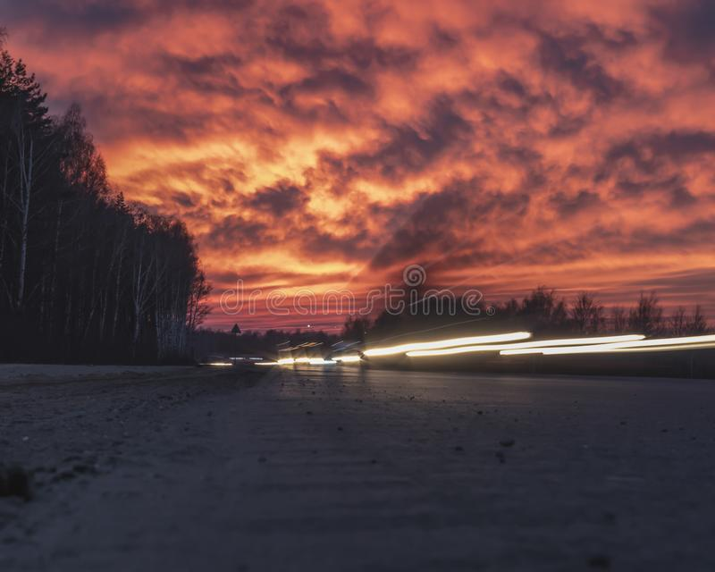 Spectacular, bright sky at sunset. Car lights photographed on long exposure. Russia royalty free stock photos