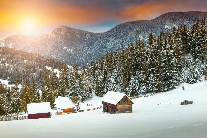 Amazing winter sunset with snowy rural wooden chalets, Transylvania, Romania. Spectacular Christmas winter landscape. Stunning colorful winter sunset, old rural stock photography
