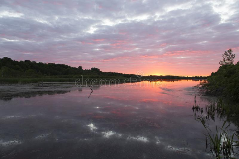 Spectacular cloudy sunrise on the Léon-Provancher marsh during springtime. Neuville, Quebec, Canada stock images