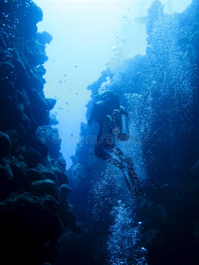 Silhouette of a scuba diver swimming out of the canyon divesite in Dahab, Egypt. At the spectacular divesite The Canyon in Dahab, Egypt, a scuba diver is stock images