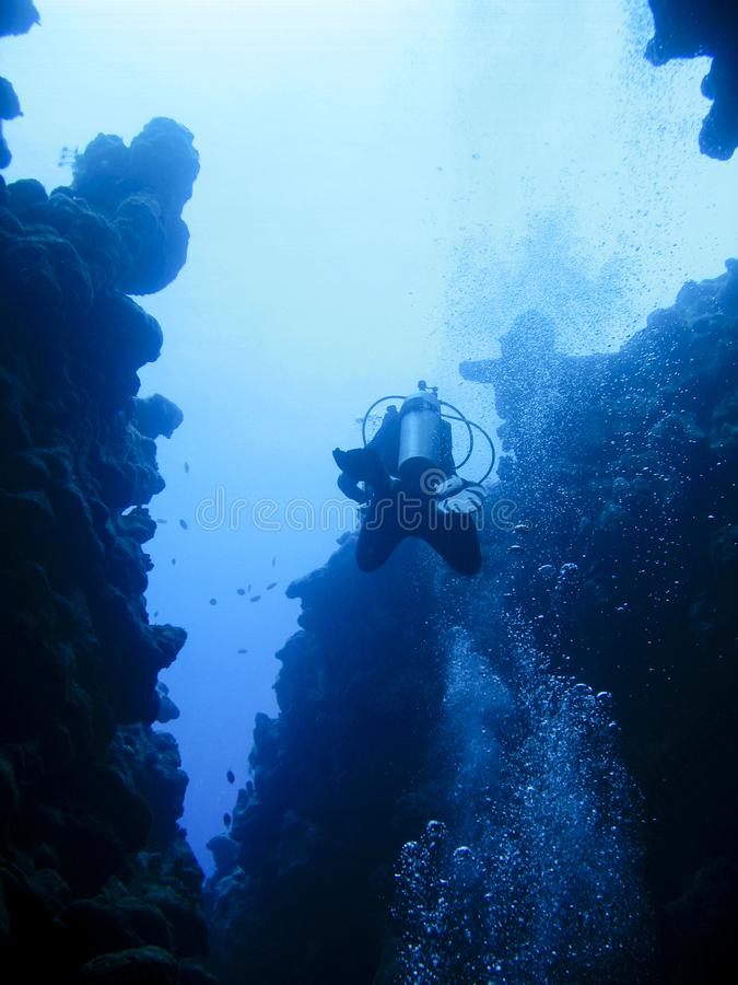 At the bottom of an underwater canyon in Dahab, Egypt. At the spectacular divesite The Canyon in Dahab, Egypt, a scuba diver is swimming in between the reef stock photos