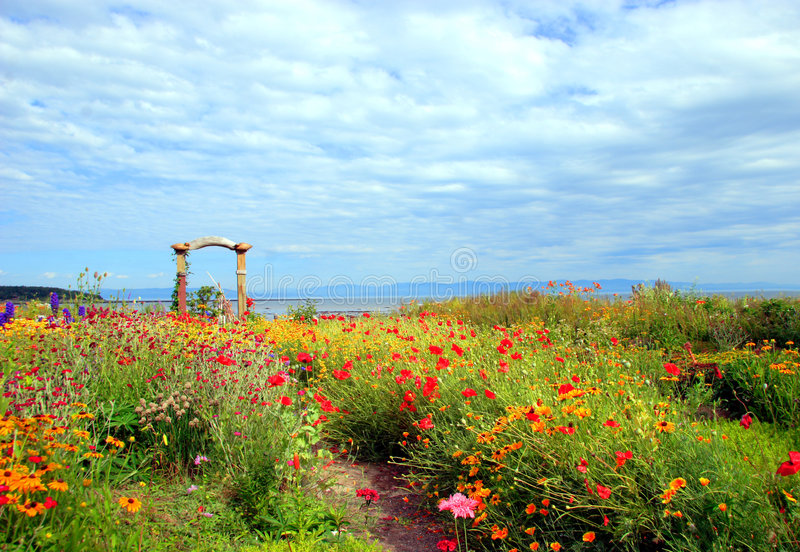 Spectacular flower garden. A impressive and spectacular flower garden near the St-Lawrence River in Kamouraska, Quebec, Canada. The background is a cloudy sky stock photography