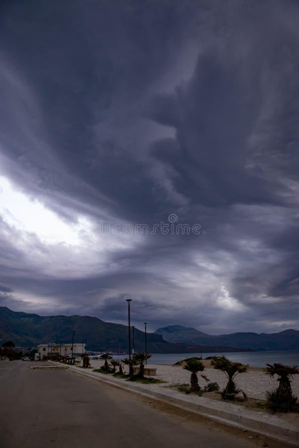 Spectacular gray cumulonimbus clouds above sea during dawn light. Spectacular low gray cumulonimbus clouds above sea during dawn light stock image