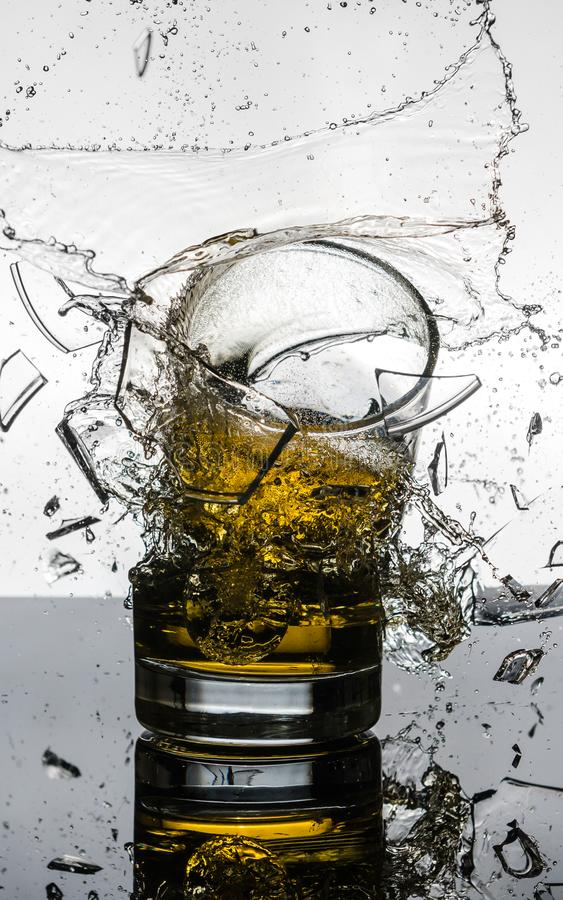 Spectacular High Speed shot of whiskey Glasees breaking. A short glass was dropped onto another one full of whiskey, and a picture was taken while they were mid stock images
