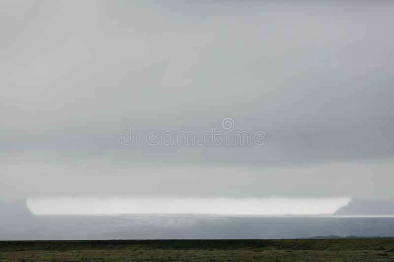 spectacular icelandic landscape with grassy plain and glacier royalty free stock photo