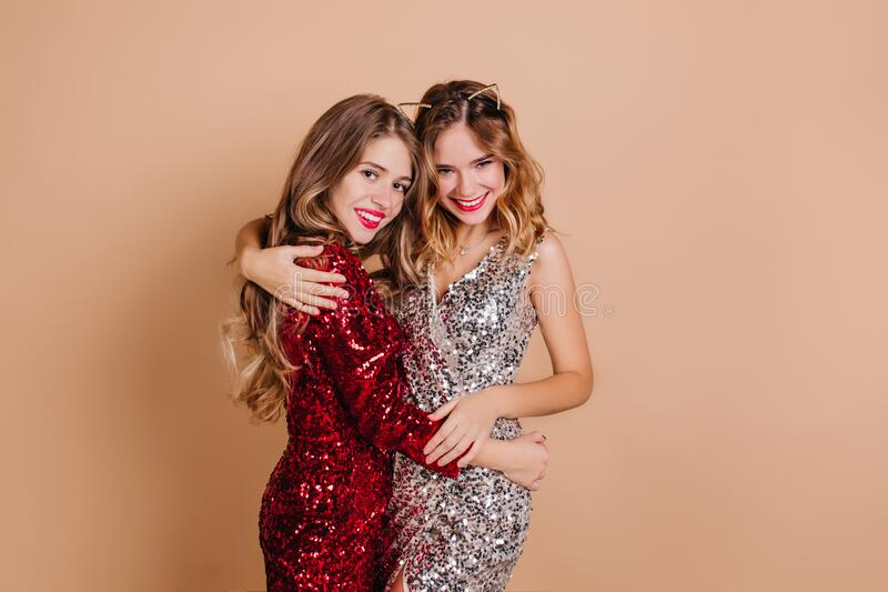 Spectacular lady embracing sister with tenderness, enjoying christmas party. Indoor portrait of cute female friends. Hugging on beige background in sparkle royalty free stock image