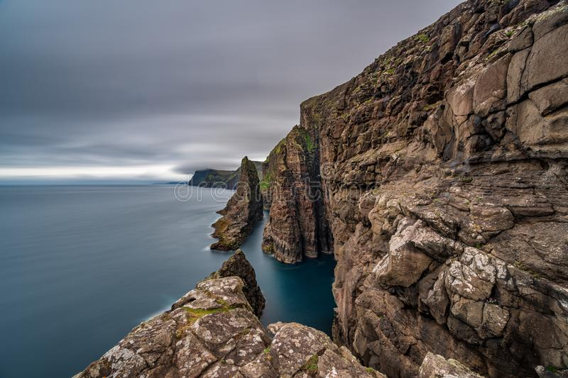 Spectacular long exposures of steep coast of Faroe Islands. Spectacular wide angle view long exposure of steep coast of Faroe Islands royalty free stock photos