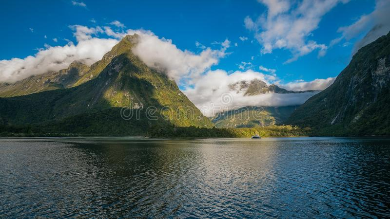 Spectacular Milford Sound mountain range surrounded by clouds close to sunset stock image