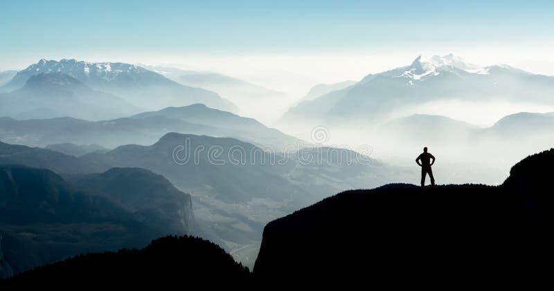 Spectacular mountain ranges silhouettes. Man reaching summit enjoying freedom. Beautiful view snow covered mountain ranges silhouettes and fog filled valleys royalty free stock photo