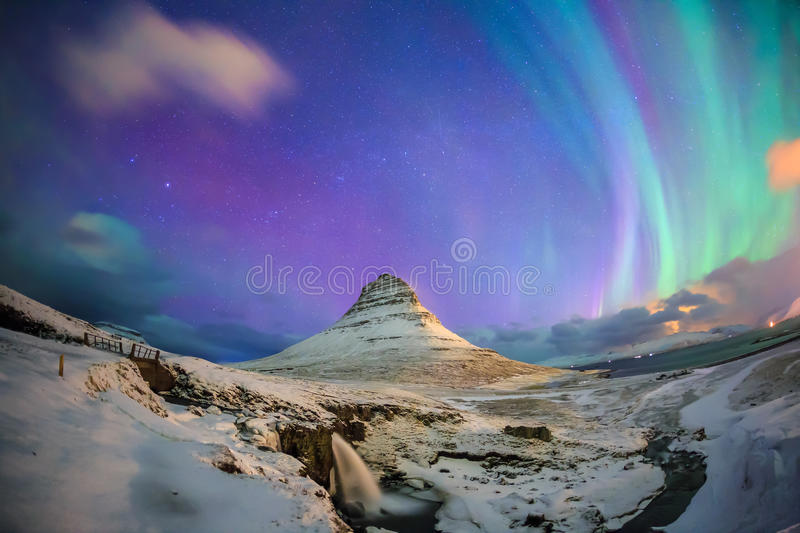 Spectacular northern lights appear over Mount Kirkjufell. And waterfall in Iceland stock images