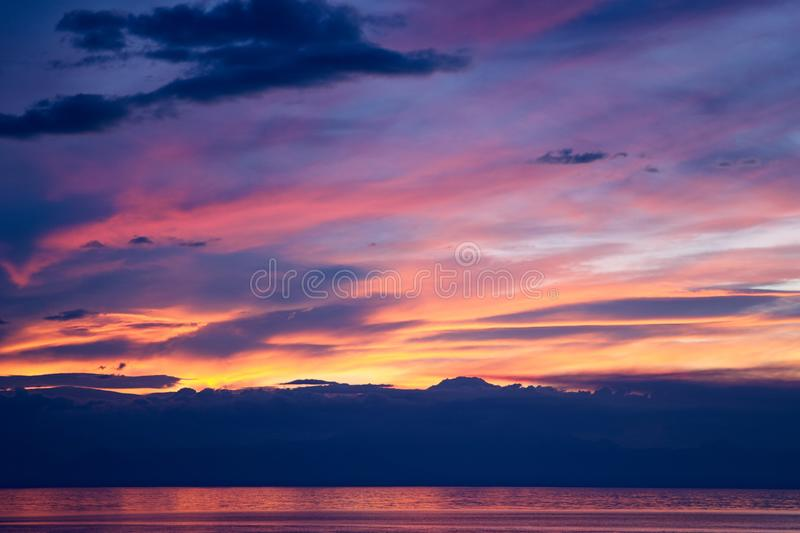 Spectacular orange and purple sunset over mountain. Spectacular orange and purple sunset over silhouetted mountains and calm water reflecting the vivid light stock photos