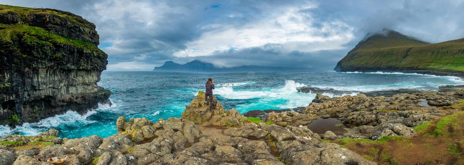 Spectacular panorama with unidentified photographer in the coastline. Spectacular panorama with unidentified photographer in the wild coastline of Faroe Islands royalty free stock photo