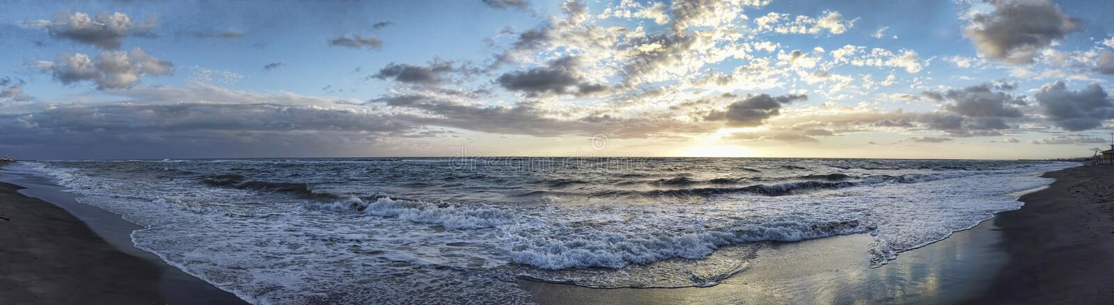 Spectacular  panoramic sunset on the Roman coast in Ostia Lido with waves breaking on the shore and  blue and golden sky spreads a. Spectacular panoramic sunset royalty free stock photo