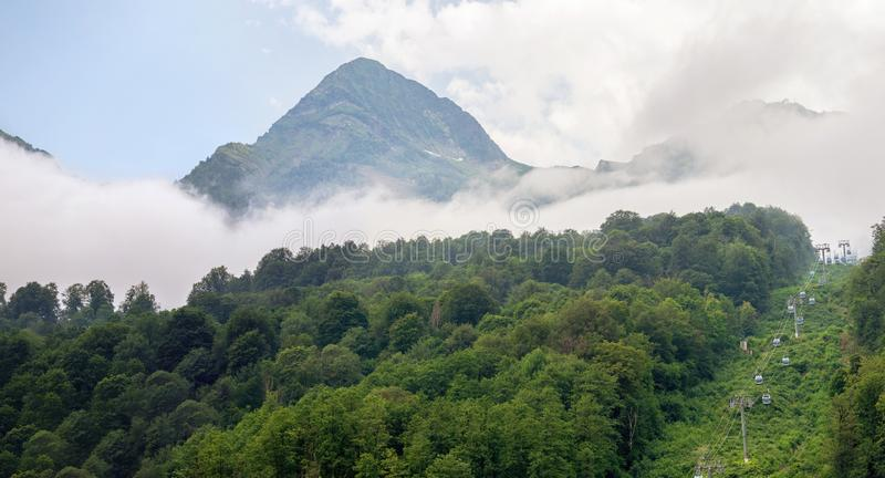 Panoramic view of green mountains with cable car and peaks in dense fog stock photography
