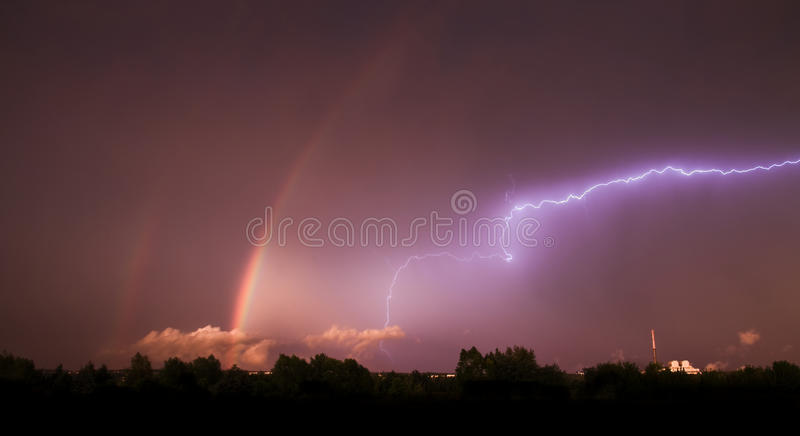 Spectacular storm. With two rainbows and thunderbolt royalty free stock image