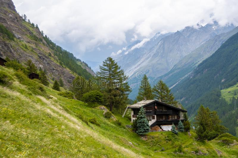 Spectacular summer alpine landscape, mountain swiss wooden chalet with high mountains in background, Zermatt royalty free stock images