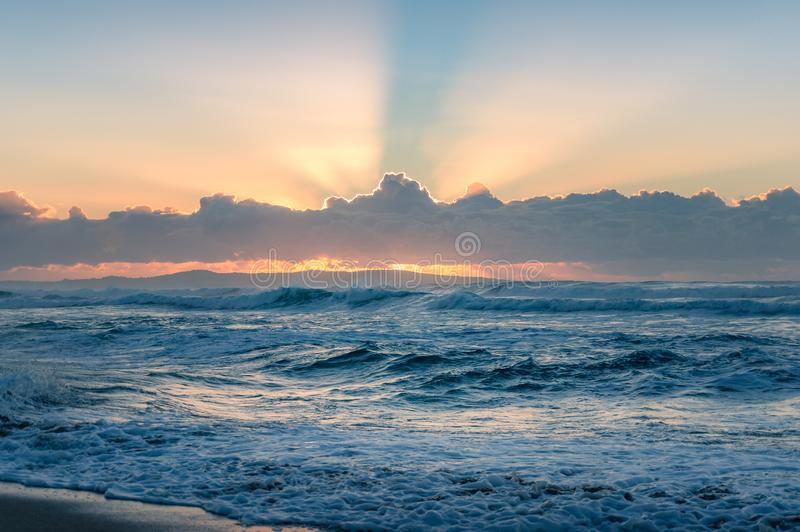 Spectacular sunrise seascape of ocean waves and sun beaming through the clouds royalty free stock photo