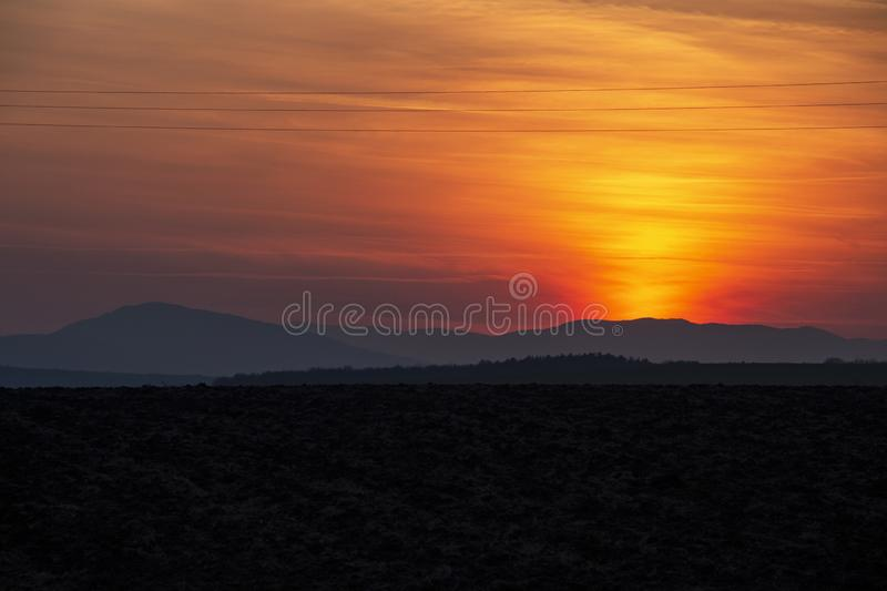 Spectacular sunset over plowed agricultural field stock photo