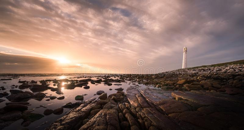 A spectacular sunset at the Slankop lighthouse at Kommetjie in Cape Town, Western Cape of South Africa. Lighthouse along rocky coastline standing tall during stock images