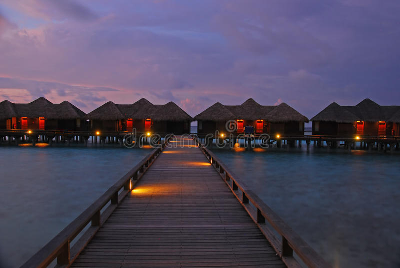 Spectacular Twilight in one of the islands at Maldives. With typical Luxury Overwater Bungalow and silky water and dramatic sky stock photos