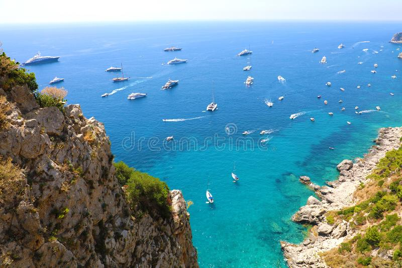 Spectacular view of Capri rocky coast with yatchs and luxury ships in blue turquoise sea, Capri Island, Campania, Italy.  royalty free stock photo