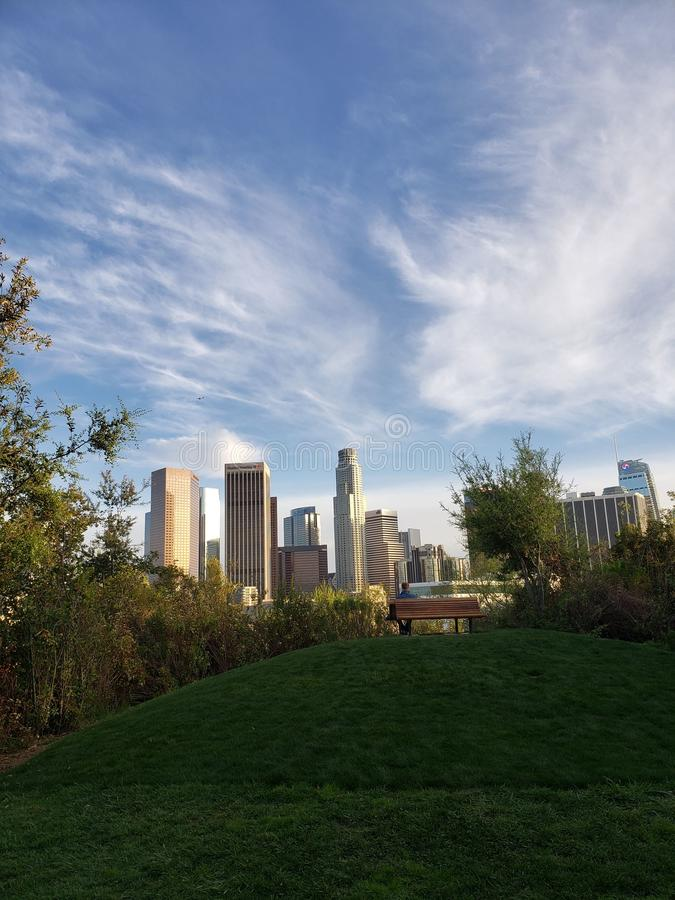 Spectacular view of downtown Los Angeles from a green park with a hill and a bench, Vista Hermosa National Park royalty free stock photos