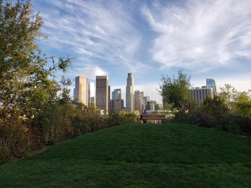 Spectacular view of downtown Los Angeles from a green park with a hill and a bench, Vista Hermosa National Park royalty free stock images