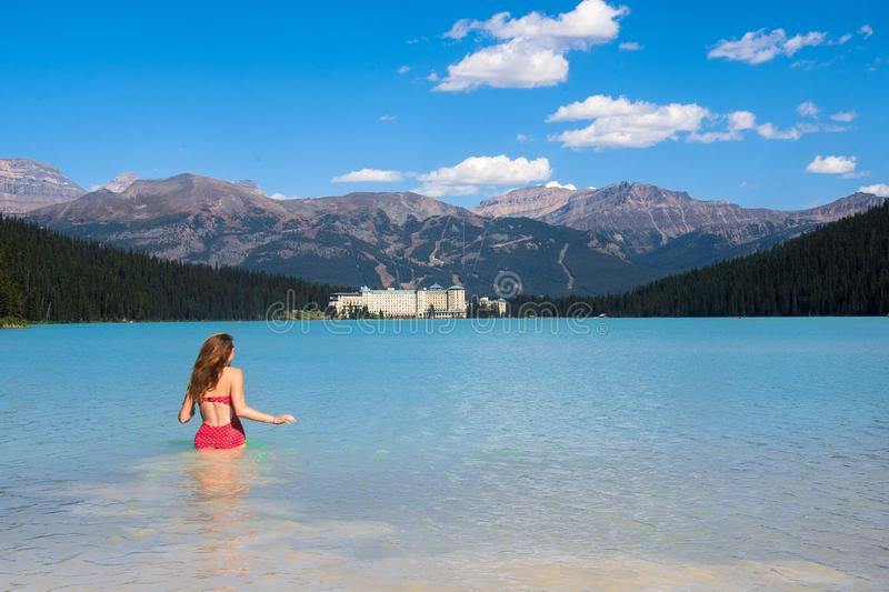 Spectacular view of the Lake Louise and Fairmont Chateau Hotel in the Rocky Mountains. A woman gonna swimming in the cold clear water of Lake Louise and looks at royalty free stock photos