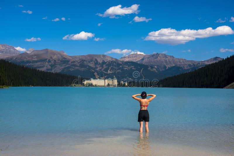 Spectacular view of the Lake Louise and Fairmont Chateau Hotel in the Rocky Mountains. A woman stands in the cold clear water of Lake Louise and looks at the royalty free stock photography