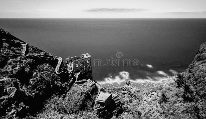 Spectacular view to the coastal ruin as long exposure and black and white art stock photo