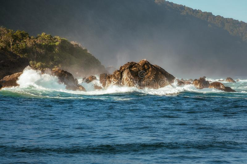 Spectacular Waves crashing on the seashore of Tasman Sea at Milf. Ord Sound fjord on a beautiful summer morning - Fiordland National Park, New Zealand, South stock image