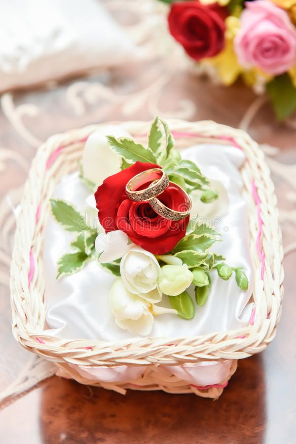 Spectacular wedding rings arrangement with red roses royalty free stock images