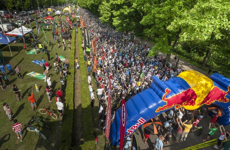 Spectateur contre les athlètes serrés prêts à commencer dans un concours de mountainbike photographie stock libre de droits