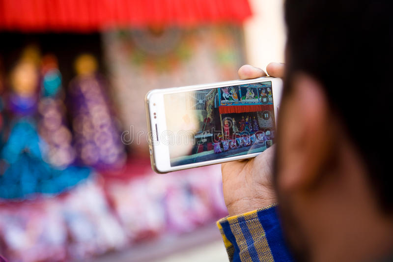 Spectator filming Kathputli. A spectator filming a Kathputli puppet show in Rajasthan with his smartphone stock image