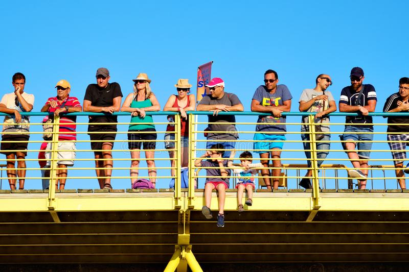 Spectators gathered together on bridge during La Vuelta race. Torrevieja, Spain - August 24, 2019: Lot of spectators gathered together on bridge against blue sky stock photography