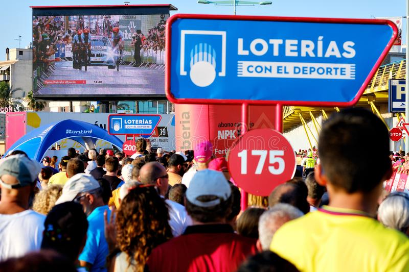 Spectators during La Vuelta international cycling watching race on television broadcasts on big screen outdoors royalty free stock image