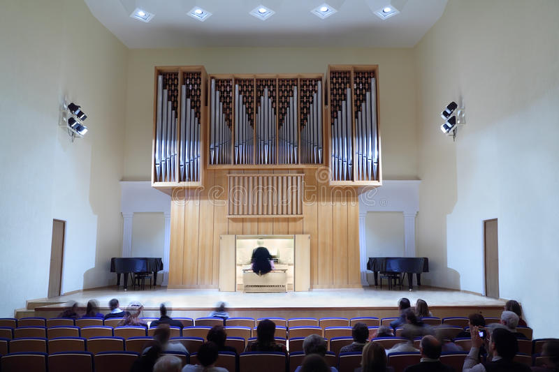Spectators are sitting and watch performance. Spectators are sitting on seats and watch performance - woman playing on large organ royalty free stock image