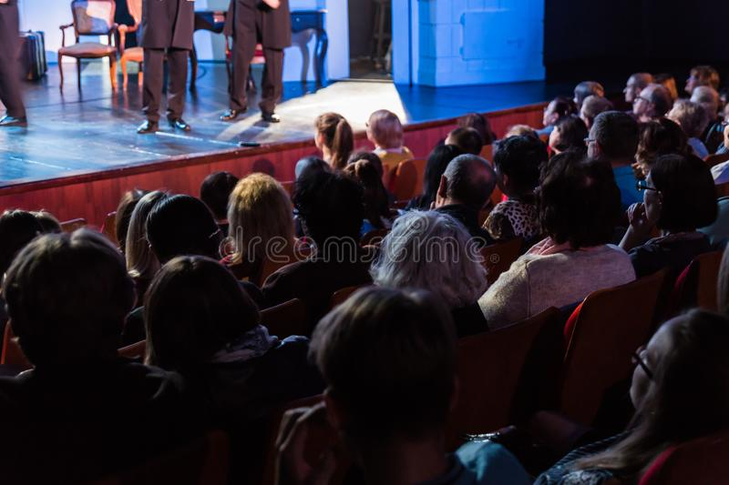 Spectators at a theater performance, in a cinema or at a concert. Shooting from behind. The audience in the hall royalty free stock image