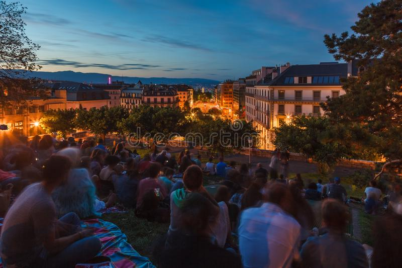 Spectators waiting for fireworks festival show at Observatory Park hill over Geneva city at dusk during beautiful summer evening,. Spectators waiting for stock photo