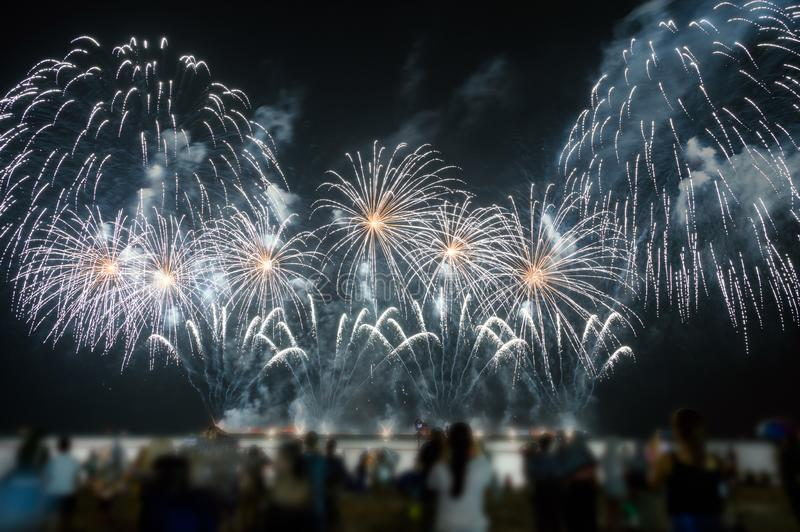 Spectators are watching colorful fireworks in the night sky on the beach stock photos