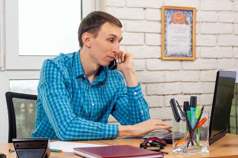 Spedizioniere che lavora in un computer portatile e che parla sul telefono fotografia stock libera da diritti