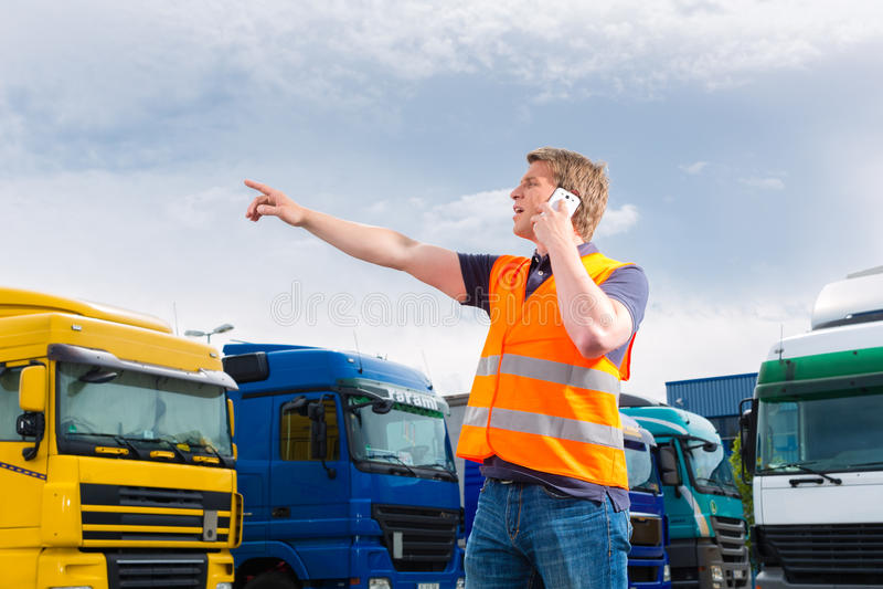 Spedizioniere davanti ai camion su un deposito immagine stock libera da diritti