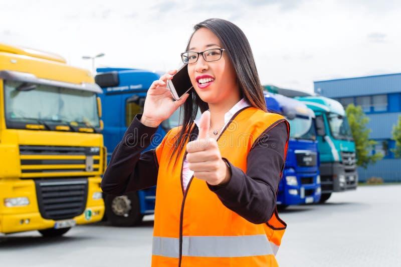 Spedizioniere femminile davanti ai camion su un deposito fotografia stock