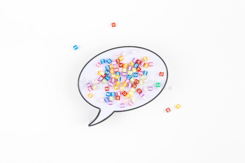 Speech bubble lightbox and multicolor alphabet. Creative flat lay back to school education concept with speech bubble lightbox and multicolor letters isolated on royalty free stock photography