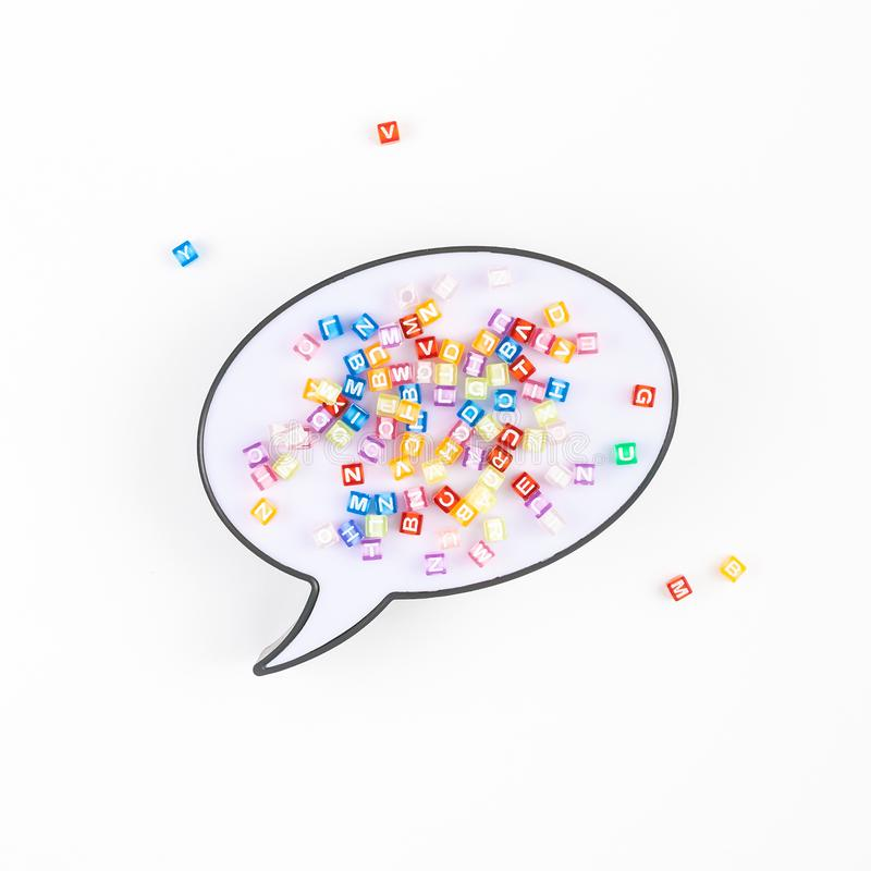 Speech bubble lightbox and multicolor alphabet. Creative flat lay back to school education concept with speech bubble lightbox and multicolor letters isolated on stock photography