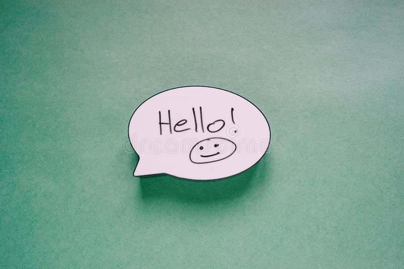 Speech bubble sign with the words Hello and Smiley. Speech message symbol on paper green background. Greeting card or invitation royalty free stock image